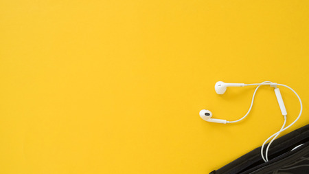Earphone and black bag on yellow background.Relax time concept