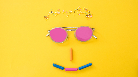Glasses and Colored Rainbow Sprinkles with marsh mallow shape smile face on yellow background.Happy smile concept