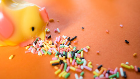 Jelly shape chicken with colored Rainbow Sprinkles selective focus on orange background creative concept. Imagens