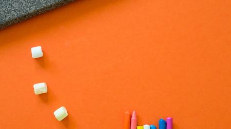 Notebook with crayon and marsh mallow on orange background copyspace Stock fotó