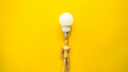 wooden dummy with light bulb on yellow background