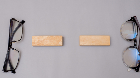 wood block and glasses on gray background copy space