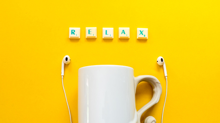 scrabble game tiles spelling relax and cup coffee on yellow background Stok Fotoğraf