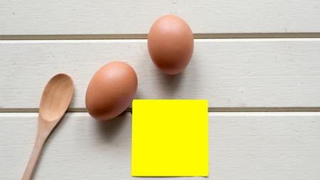 egg with  sticky note close up on wood background Фото со стока