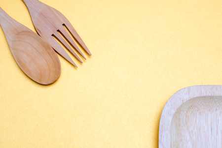 spoon and fork and dish on yellow background Фото со стока