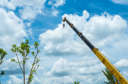 Industrial Crane operating and lifting an electric generator against and blue sky