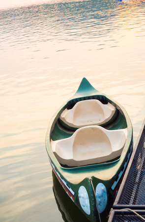 tied, empty canoes lie in a row next to each other in a river