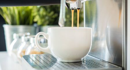 coffee machine espresso looking fresh coffee into a neat ceramic cup