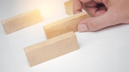 Close up man hand put wooden blocks in the shape on white background
