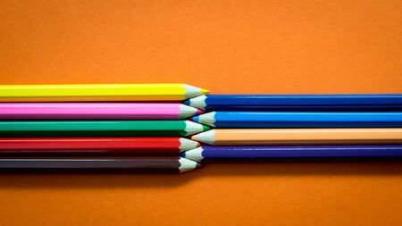 Set of multicoloured  pencil or crayon on orange background. Top view
