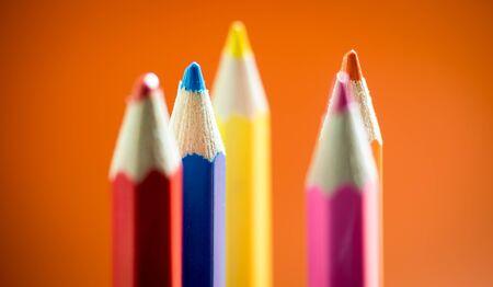 Set of multicoloured  pencil or crayon on orange background. Selective focus
