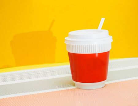 Red coffee cup with shadow yellow background.Modern concept