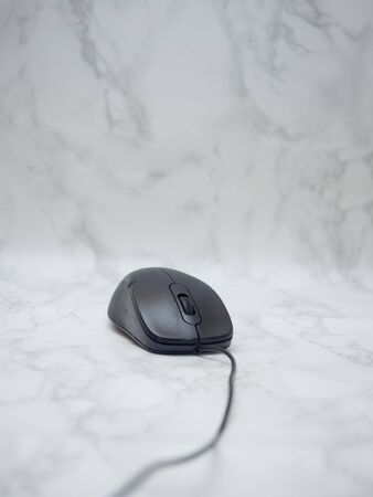 A black mouse on a marble floor