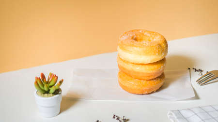 Homemade deep fried donuts in stack with sugar standing on crumpled paper with white table.
