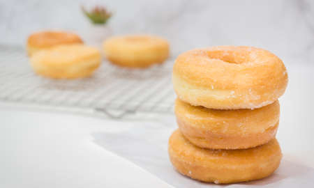 Homemade deep fried donuts in stack with sugar standing on crumpled paper wooden with marble table.
