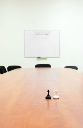 perspective room: White and black pawns standing face to face on meeting table. Stock Photo