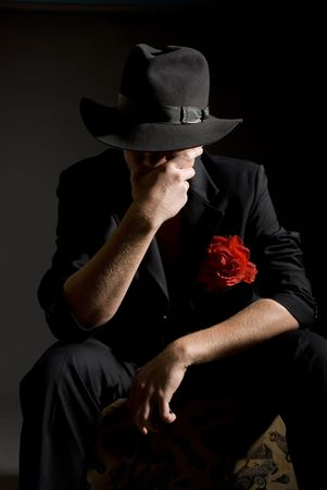 noir: man in black suite and with red rose
