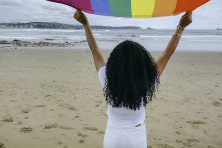 Woman holding the Gay Rainbow Flag on the beach outdoors. Happiness, freedom and love concept for same sex couples. Image