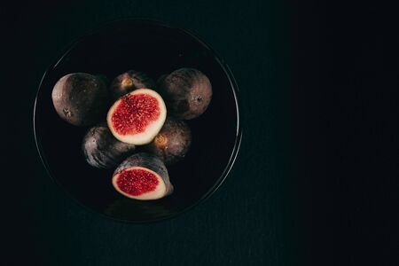 Tasty and fresh ripe fig fruits on black background, top view. Tropical fruit. Space for text