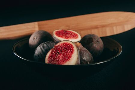 Black bowl of fresh figs on dark background and cut with a knife