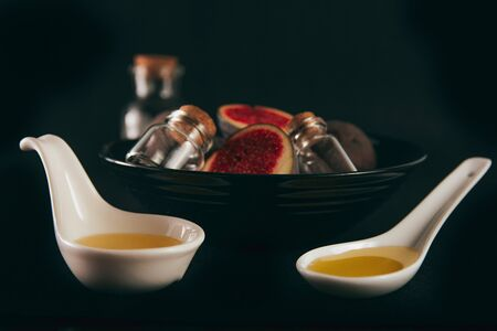 Fresh and natural figs in a black bowl with crystal bottles and olive oil. Space for text