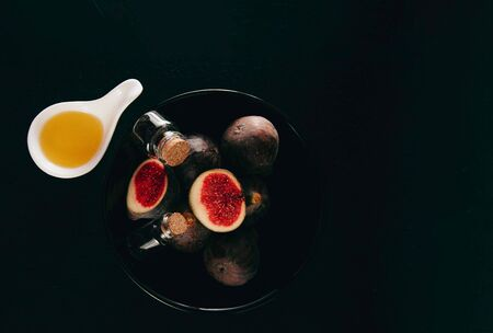 Fresh and natural figs in a black bowl with crystal bottles and olive oil, top view. Space for text