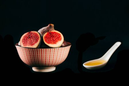 Bowl with fresh ripe figs olive oil on black background, front view, Space for text