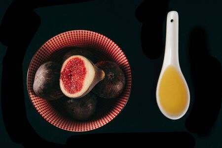 Bowl with fresh ripe figs with olive oil on black background, top view, Space for text Stock fotó