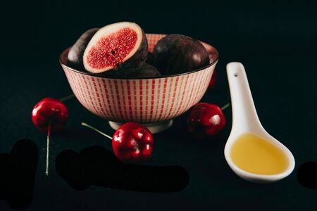 Bowl with fresh ripe figs and sweet cherry on black background. Space for text