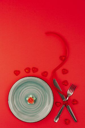 Festive table setting for Valentines Day on red background. Valentine's day concept. Top view.