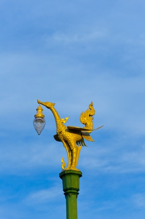 Golden swan statue with blue sky