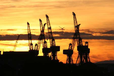 chantier naval: Les grues d'un chantier naval silhouetted Clyde � Glasgow par un coucher de soleil