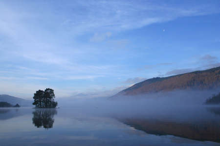 forested: A misty Loch Tay with a small, forested island and the Moon in the sky