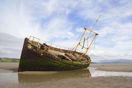derelict: A derelict fishing boat lit by evening sunshine at Ettrick Bay, Bute