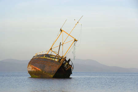 derelict: A derelict fishing boat lit by morning sunshine off the coast of Bute