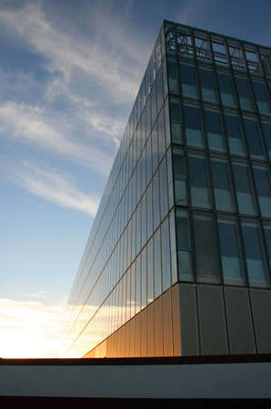 superstructure: Glass faced building below cirrus clouds at sunset