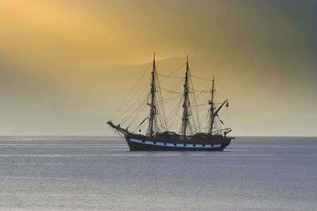 Tall ship anchored in a calm sea lit by morning light Stock Photo - 533240