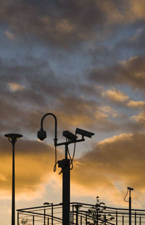 electronic survey: Security cameras silhouetted against an evening sky Stock Photo
