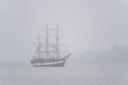 Tall ship seen in the morning mist photo