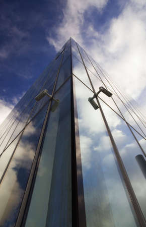 Corner of glass faced office building reflecting sky photo