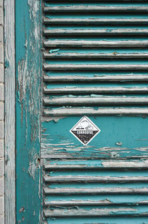 tatty: Tatty door with peeling paint and a warning sticker Stock Photo