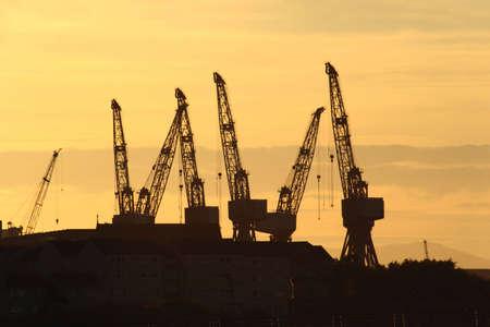 construction navale: Construction navale grues silhouetted contre un coucher de soleil Glasgow