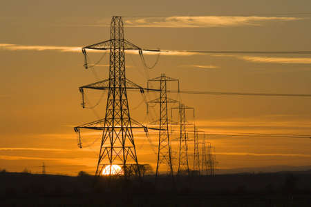 pylons: Sun setting behind a row of electricity pylons