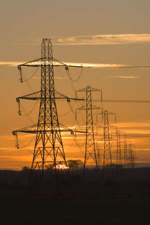 Sun setting behind a row of electricity pylons Stock Photo - 760652
