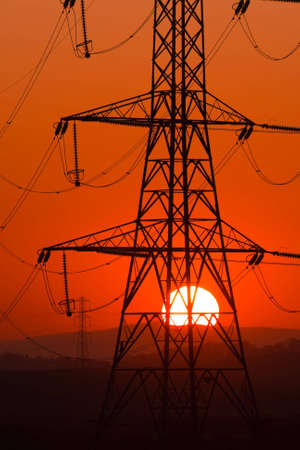 conductor electricity: Setting Sun seen through an electricity pylon