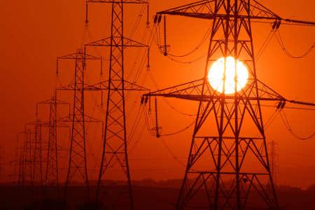 the setting sun: Setting Sun seen through a row of electricity pylons