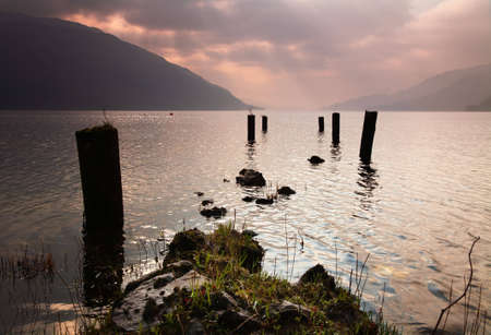 loch lomond: Supports for old jetty lead out into Loch Lomond Stock Photo