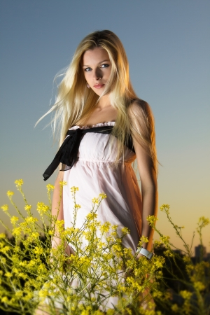 A girl in a pink dress in the flowers, at sunset