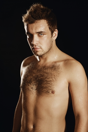 Wet man isolated on a black background, with a hairy chest