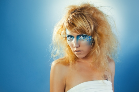 Beautiful girl with sea shells on the face, on a blue background